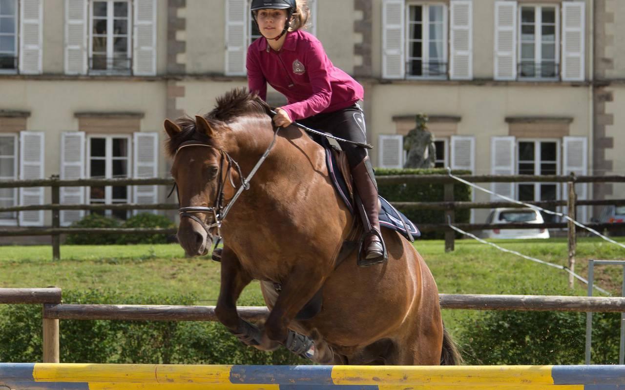 saut d'obstacle d'une jeune fille, cours stages centre équestre auvergne, Château d'Ygrande.